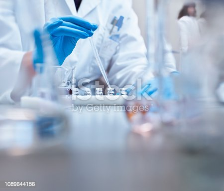 Scientist filling vials with solution through pipette in test tube rack. Chemist is examining medicine during scientific experiment. She is wearing gloves at pharmaceutical factory.