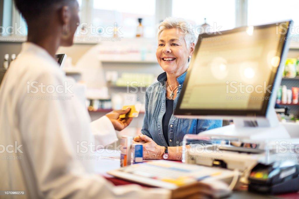 Chemiker der Karte an Kunden zu geben, nach der Zahlung – Foto