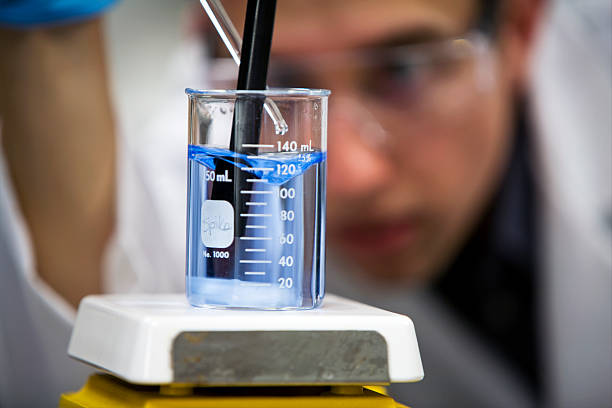 Chemist in Lab Focus on Beaker Close Up A chemist tests for water quality. Focus on beaker. sewage stock pictures, royalty-free photos & images