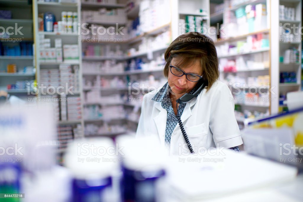 Chemist on the phone in pharmacy stock photo