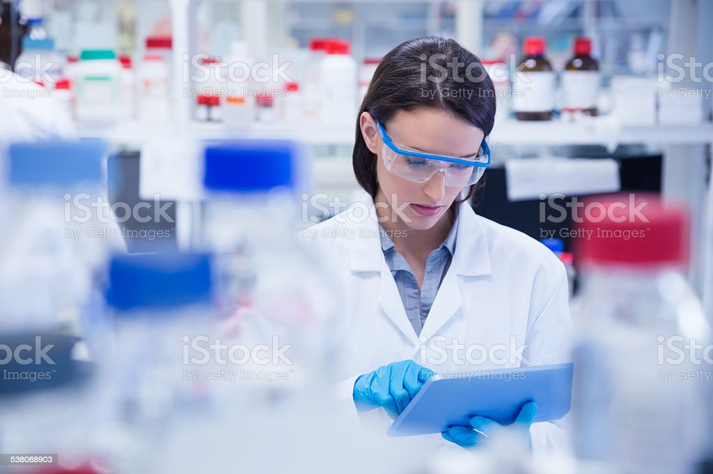Chemist wearing safety glasses and using tablet pc stock photo