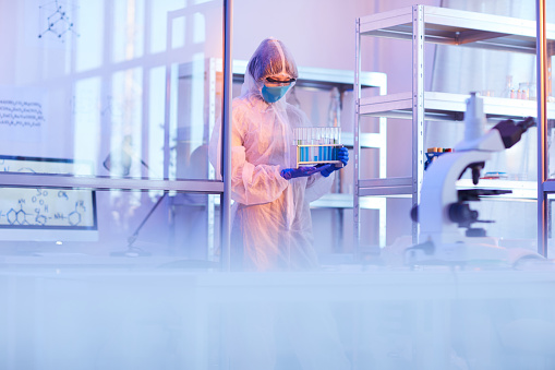 Chemist in protective costume carrying test tubes with samples she working at the medical laboratory