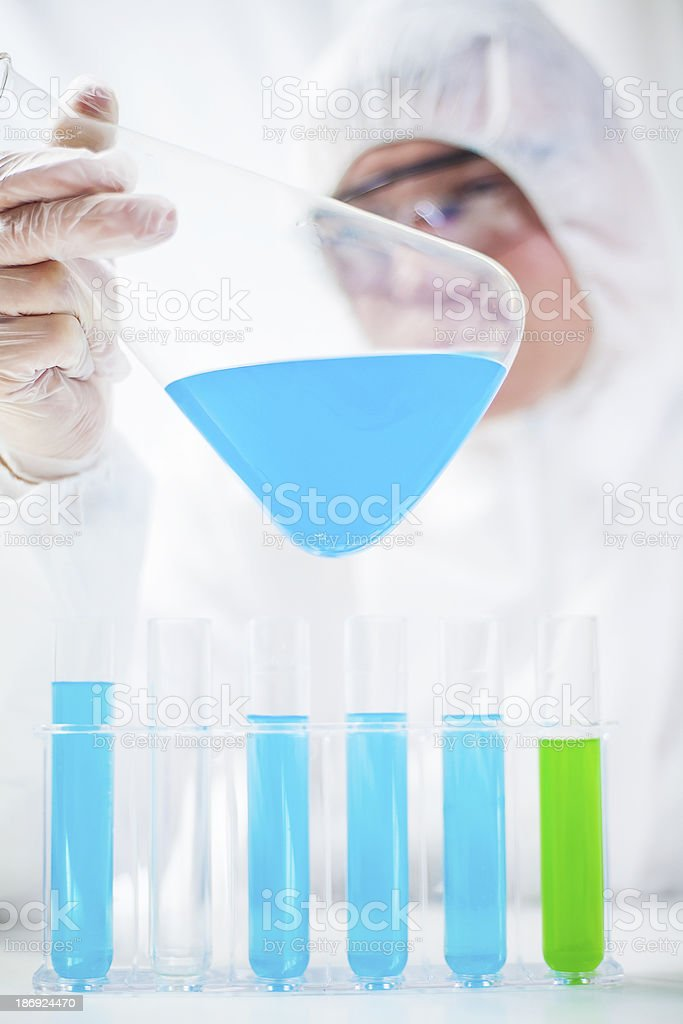 Chemist working in laboratory examining fluids stock photo