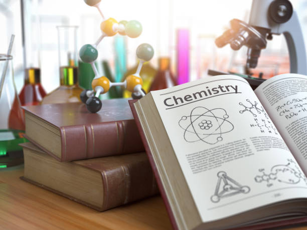 Chemistry education concept. Open books with text chemistry and formulas and textbooks, flasks with liquids and microscope in a classroom or a laboratory. stock photo