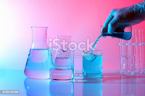 1097010784istockphoto Chemistry laboratory, hand picking flask pouring blue liquid, test tubes 475415235