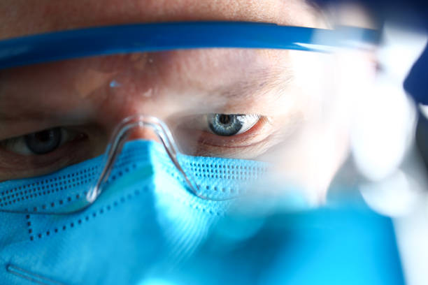 Chemistry man wearing protective mask hold in hand test sample stock photo