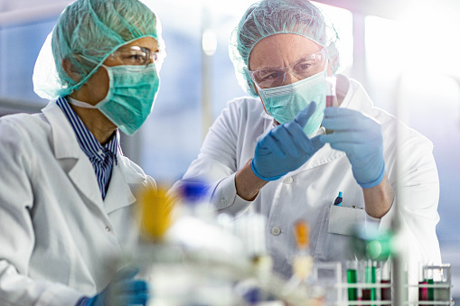 Two scientists cooperating while examining antiviral drug in a test tube at laboratory. Focus is on man.