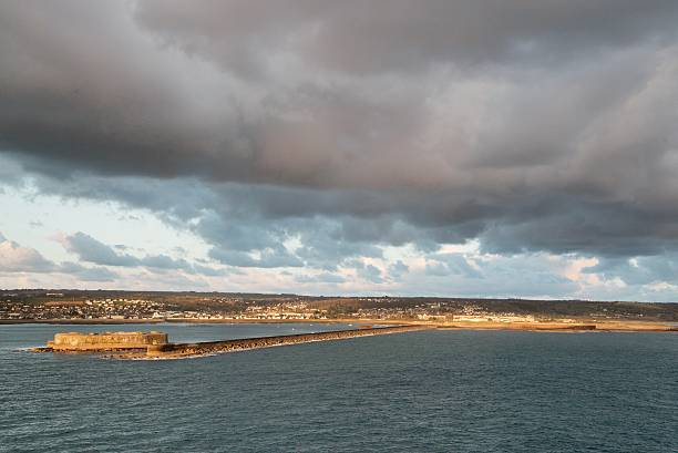 Cherbourg Inner Harbor Fortress and Jetty An old historical fort guards the inner harbor of Cherbourg at the end of a long jetty with a village along the shore in the background cherbourg stock pictures, royalty-free photos & images