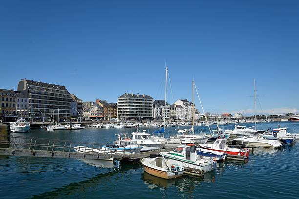 Cherbourg Marina and Quay Caligny Looking across Cherbourg marina or, Bassin du Commerce, to Quay Caligny with all the boats on a bright spring day in Cherbourg. Incidental people, restaurants, shops and apartment line the Quay. cherbourg stock pictures, royalty-free photos & images