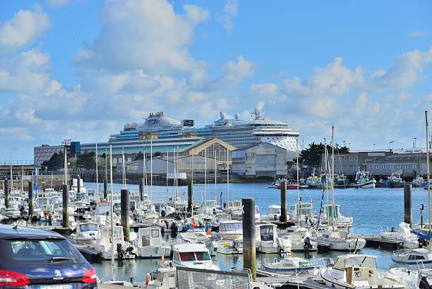 Cherbourge Marina and Cruise Ship Cherbourg, France - April 27, 2016: A very large cruise ship, the Regal Princess, docked in Cherbourg, France with the town marina in the foreground with all of its sailboats, yachts, cabin cruisers and fishing trawlers in the foreground and the French powder blue sky and cumulus clouds. cherbourg stock pictures, royalty-free photos & images