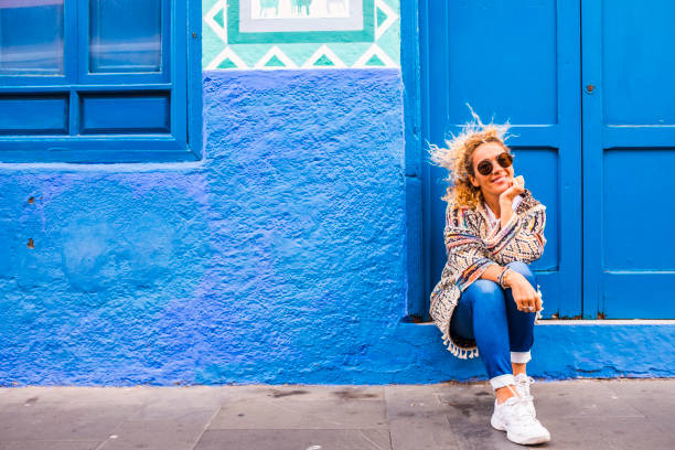 Chererful and relaxed beautiful woman sit down outside a colorful blue house in the street - home properties owner people concept - travel lifestyle and scenic places to discover stock photo