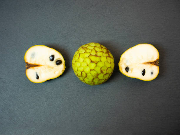 Cherimoya still life, annona cherimola on black slate background. Whole fruit and cut in half with seeds in sight. Tropical exotic fruit. Flat lay creative composition. Top view. Minimal design. stock photo