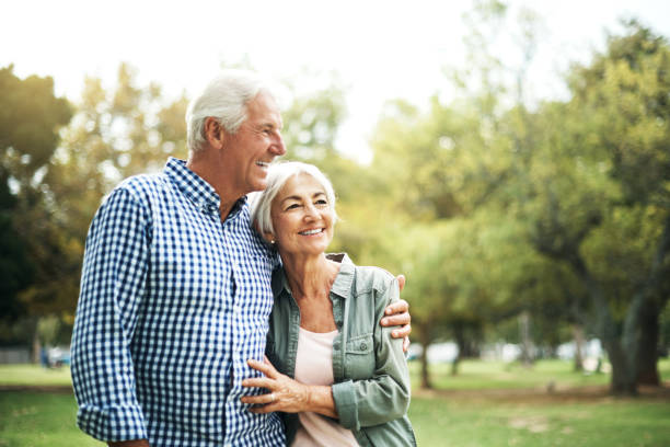 Cherish the people who make your heart smile Shot of an affectionate senior couple spending a day in the park senior couple stock pictures, royalty-free photos & images