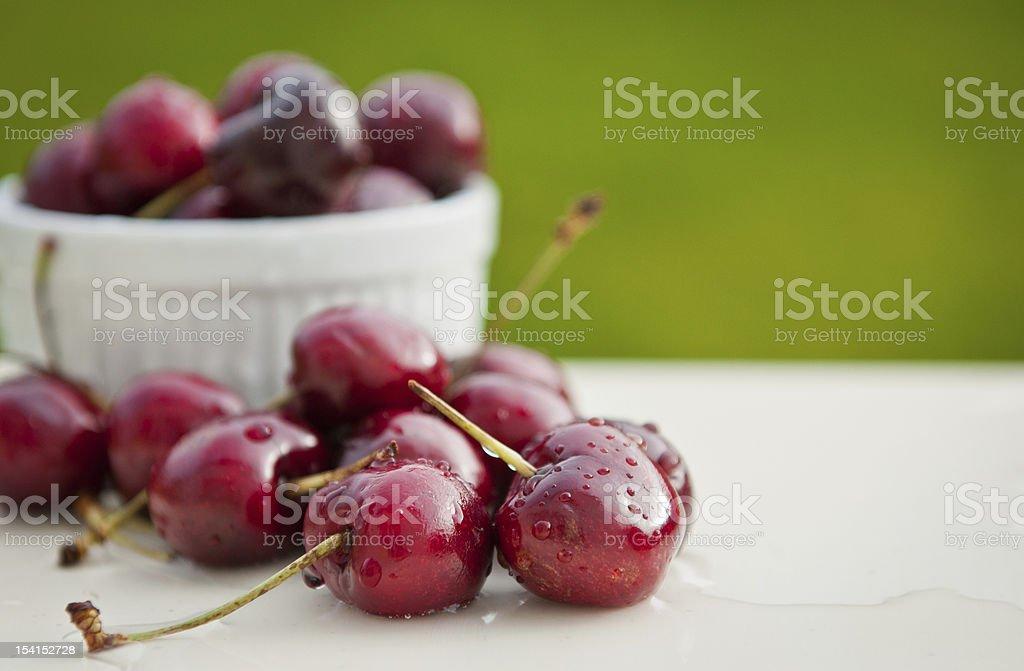 Cherries in ceramic dish on white table stock photo