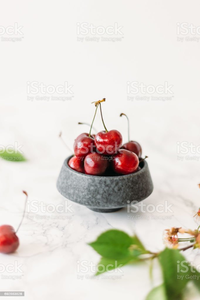 Cherries in rustic color bowl and kitchen napkin. healthy food summer concept stock photo