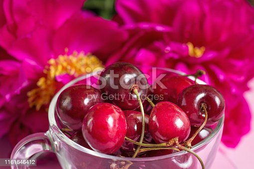 Cherries in the glass cup with peony. Close up. Beautiful summer season. Harvest concept. copy space.