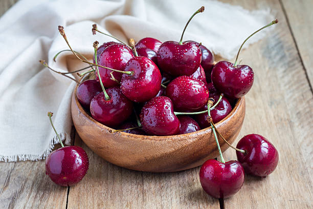 Cherries in wooden bowl with water drops, on table, horizontal stock photo