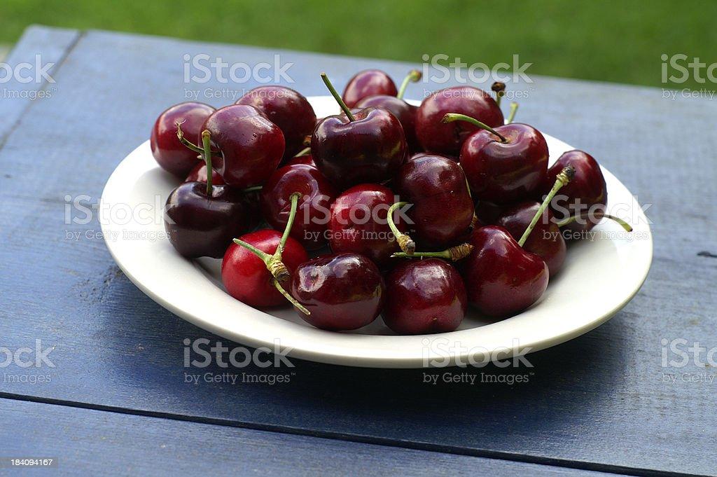 Cherries on Blue Table stock photo