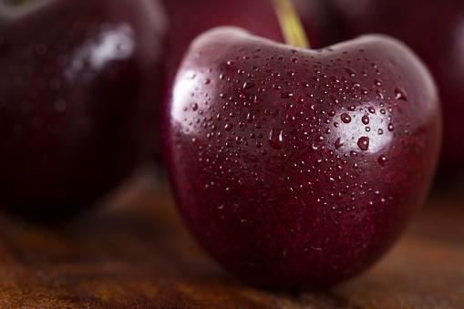Cherries on dark wooden background. Macro photo with selective focus.