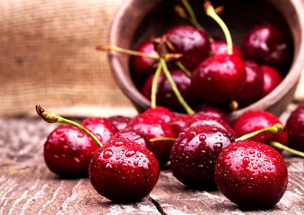 cherries on wooden table - 車厘子 個照片及圖片檔