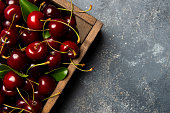 Fresh cherries in a wood container on the paint background.