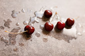 A moody photo of deep red wet cherries on a gray marble coaster. Natural light giving a bright glossy look with shadows.
