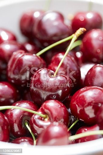 A full frame shot of cherries. Some still have their stems attached and others don't. The sun is reflected in the fruit.