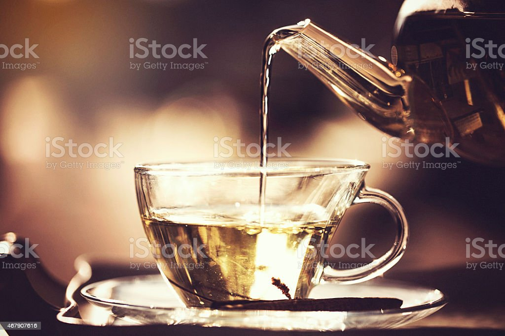 Cherries tea poured from Glass tea pot to glass cup stock photo