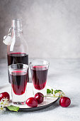 Cherry alcohol drink liquor or brandy on a pink background