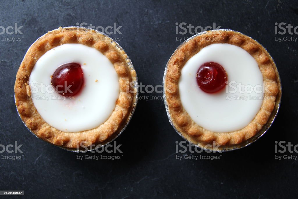 Cherry bakewell tarts in foil case on dark background looking like eyes stock photo