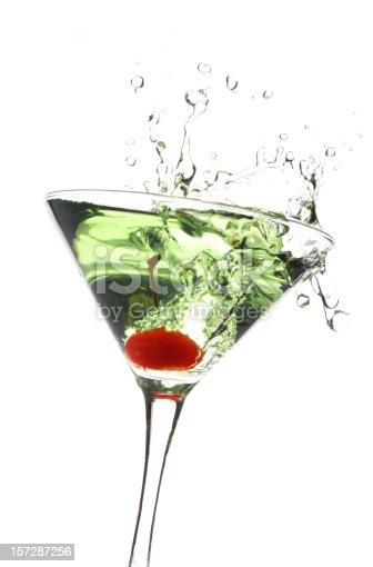 Green apple martini with a cherry splashing