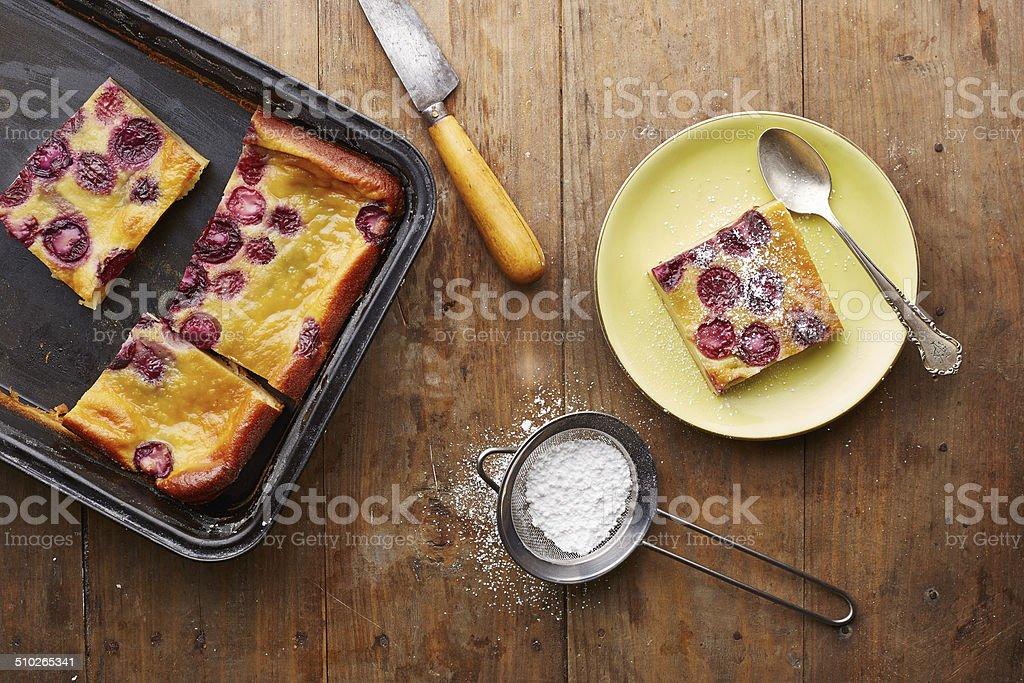 Cherry clafoutis pie on wooden table stock photo