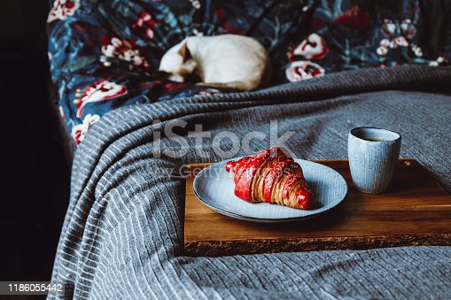 539672394 istock photo Cherry croissant with a cup of espresso on a wooden tray in a bed. The concept of cozy morning at home. 1186055442