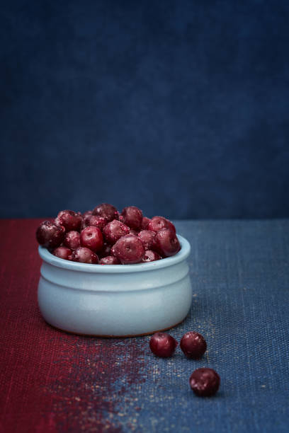 Cherry in a blue bowl on a blue background stock photo