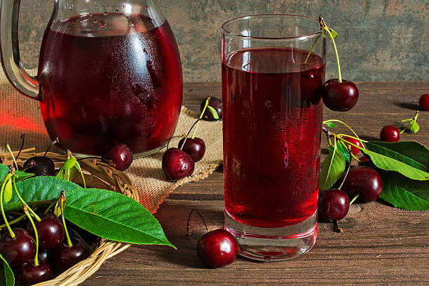 cherry juice in a glass and pitcher with cherries inside - kwaśny smak zdjęcia i obrazy z banku zdjęć