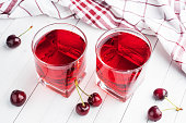 Cherry juice in glass glasses with fresh cherry berries. White background. copy space