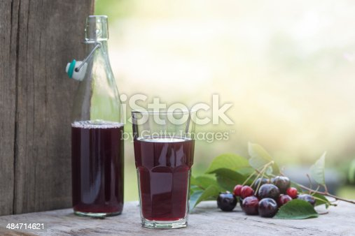 Homemade cherry juice on a rustic background decorated with cherries and leaves.