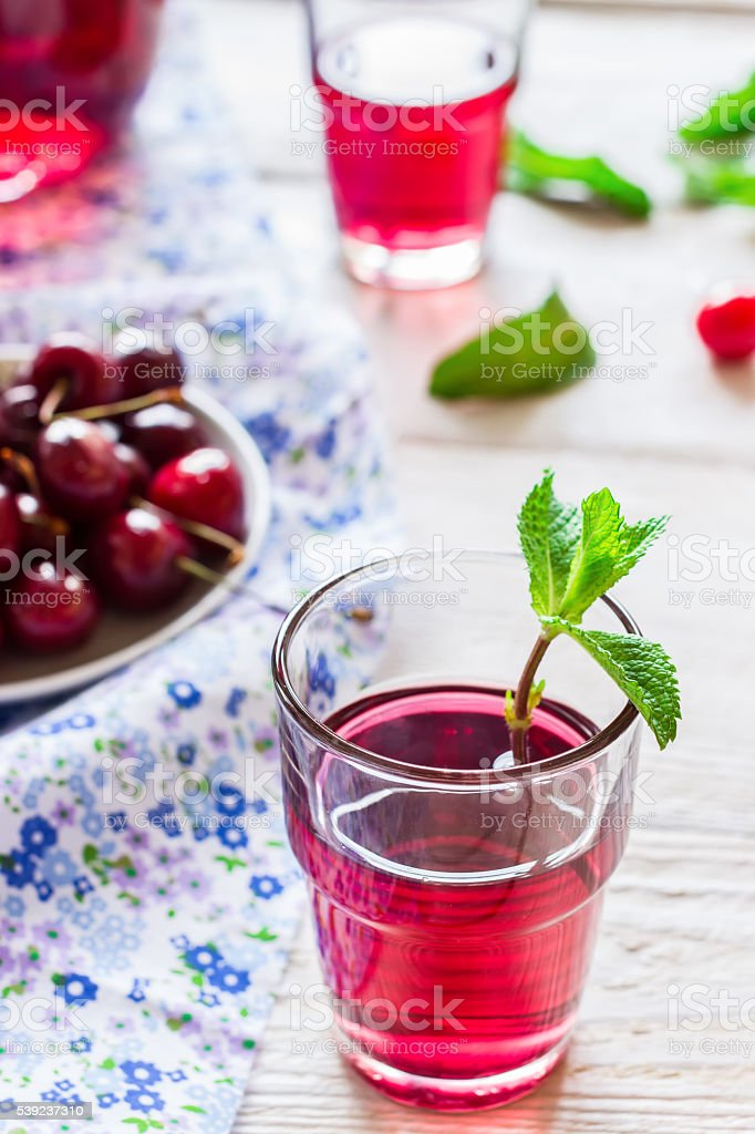 Cherry lemonade with mint on white wooden background. royalty-free stock photo