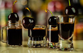 Cherry liqueur and juicy ripe cherries on the table in  the bar, an elegant serving of sweet drink in the restaurant, a traditional drink