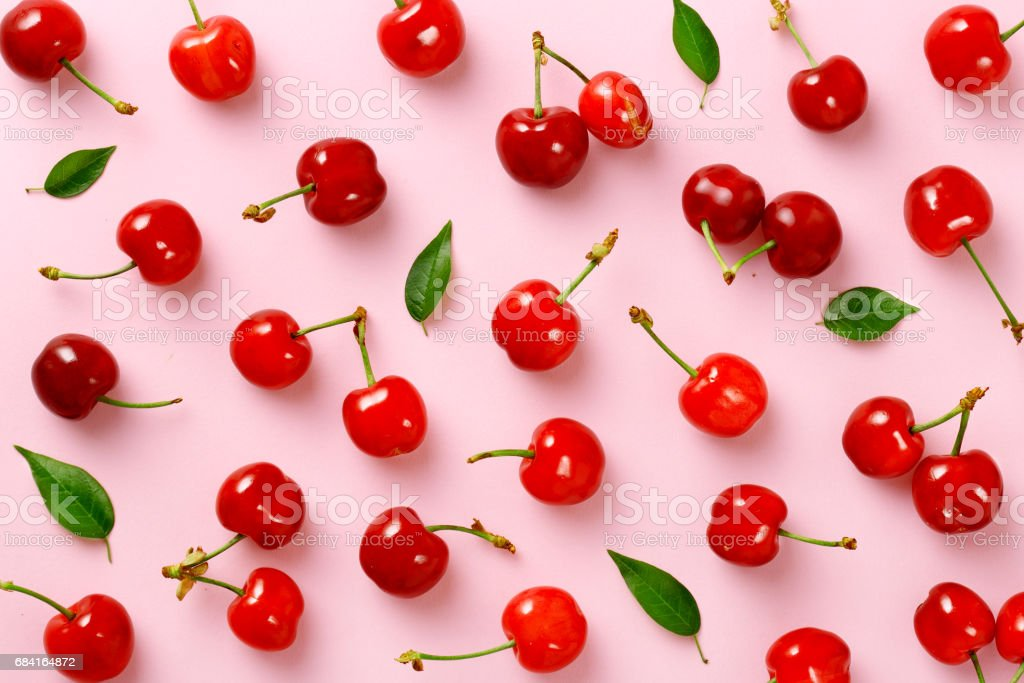 Cherry pattern. Flat lay of cherries and leaves on a pink background.Top view royalty-free stock photo