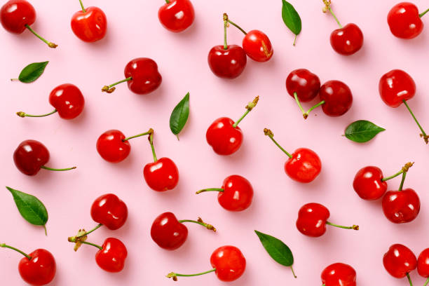 Cherry pattern. Flat lay of cherries and leaves on a pink background.Top view stock photo