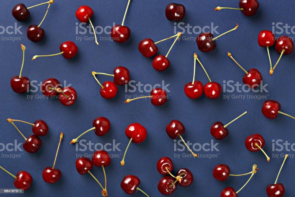 Cherry pattern. Flat lay of cherries on a dark blue background.Top view zbiór zdjęć royalty-free