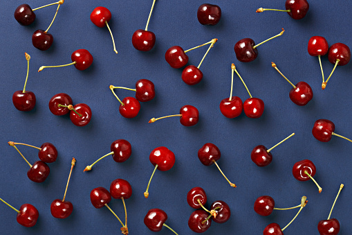 istock Cherry pattern. Flat lay of cherries on a dark blue background.Top view 684167912