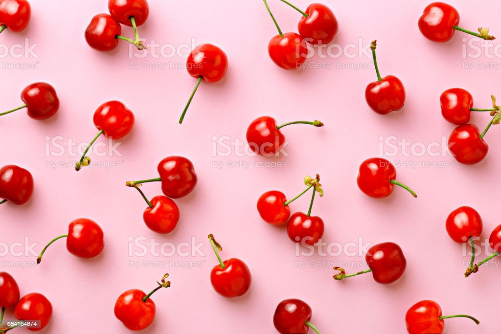 Cherry pattern. Flat lay of cherries on a pink background.Top view stock photo