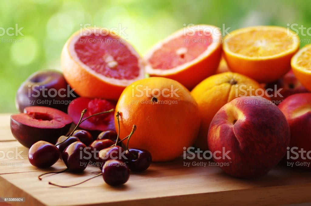 cherry, peaches and citric fruits on table stock photo