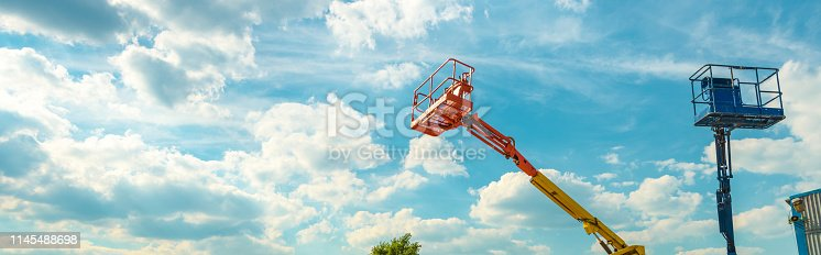 istock Cherry pickers on blue sky background 1145488698