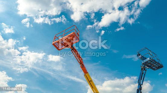 istock Cherry pickers on blue sky background 1145489217