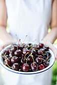 Caucasian female is holding a plate full of cherries.