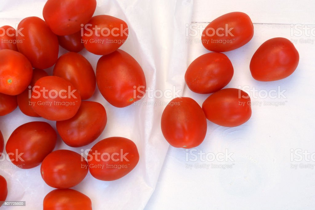 Cherry plum snack tomatoes on a white wooden background. Close-up and top view. stock photo