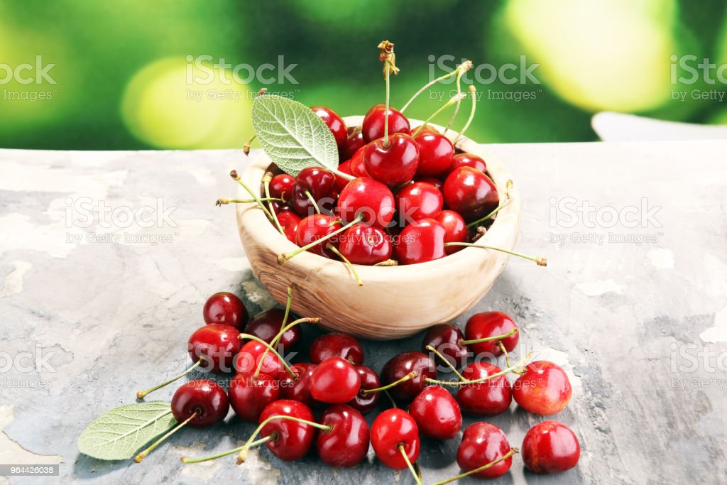 Cherry. Red fresh Cherries in bowl and a bunch of cherries on the table - Royalty-free Basket Stock Photo